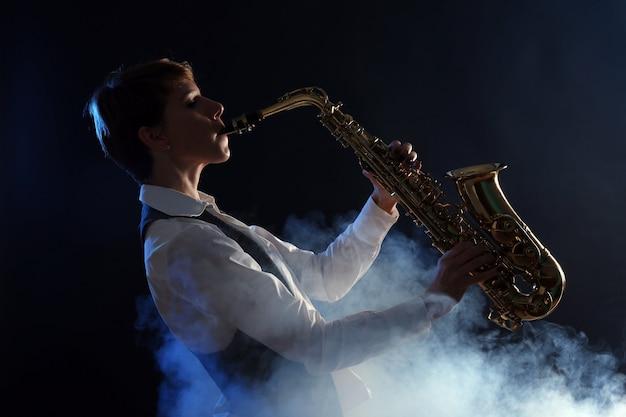 La donna attraente suona il sassofono nel fumo