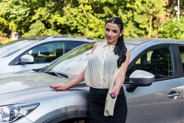 Donna attraente in posa vicino alla macchina con le chiavi