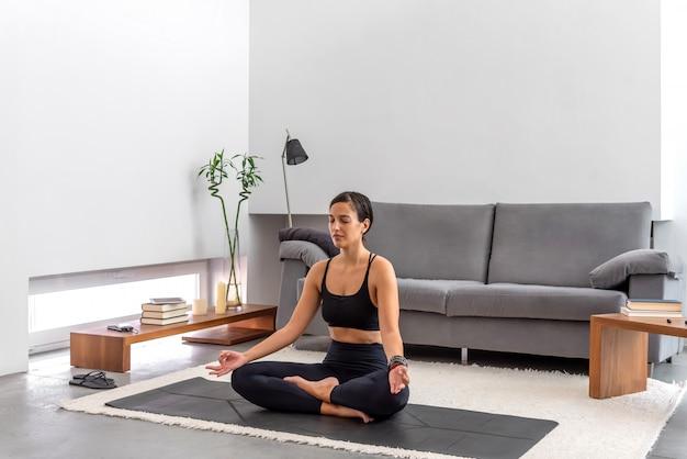 Posa di pratica del loto di yoga della donna attraente alla meditazione a casa accogliente