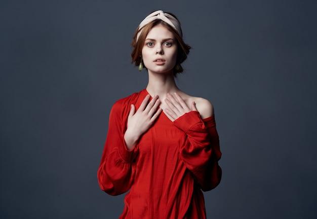 Donna attraente in abito rosso festa di lusso sfondo scuro