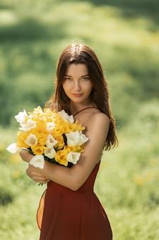 Attraente donna in abito rosso con un bouquet di fiori primaverili contro natura bokeh verde