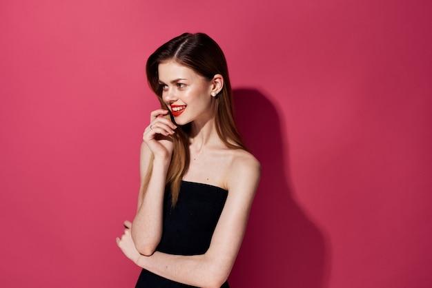 Attraente donna labbra rosse glamour lusso abito nero sfondo rosa. foto di alta qualità