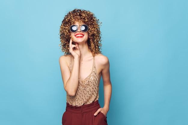 Donna attraente labbra rosse sorriso occhiali scuri studio trucco luminoso muro isolato