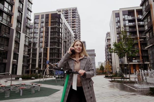 Una donna attraente guida uno scooter e racconta alla sua amica i vantaggi del noleggio di un veicolo elettrico. scooter elettrico. parlando sullo smartphone. blocchi di appartamenti moderni su priorità bassa.
