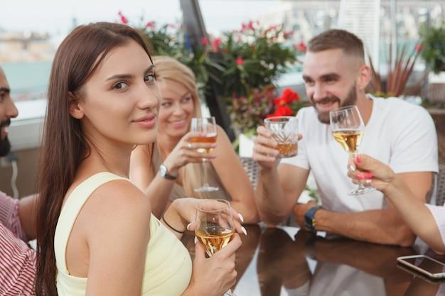 Donna attraente che sorride alla macchina fotografica mentre beve con i suoi amici al bar sul tetto