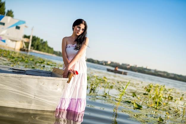 Donna attraente che sta vicino alla barca in acqua