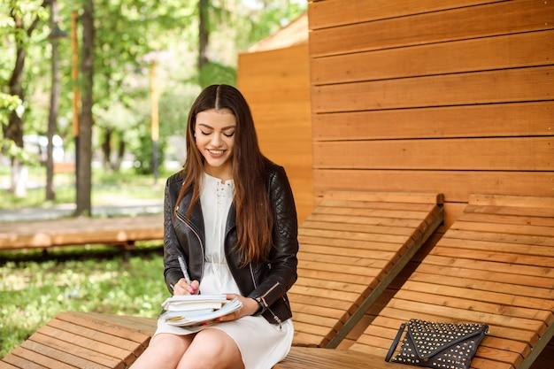 Donna attraente, studentessa sta scrivendo qualcosa nel suo libro di testo, taccuino seduto sulla panchina all'aperto nel parco.