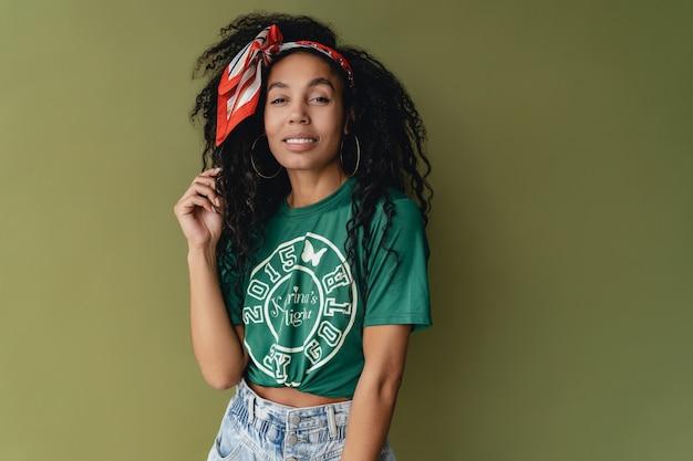 Donna attraente in t-shirt e pantaloncini alla moda hipster sulla parete verde dello studio