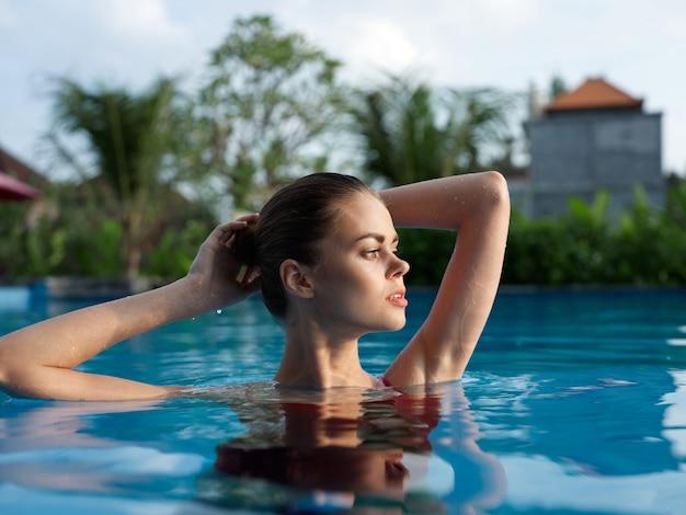 Attraente donna in costume da bagno nuota in piscina in natura con le mani alzate