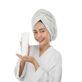 Donna attraente in asciugamano con la mano che presenta la bottiglia del tubo bianco