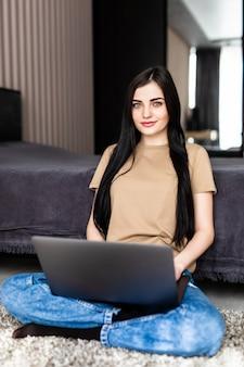 Donna attraente che usa un computer portatile, seduta sul pavimento del soggiorno