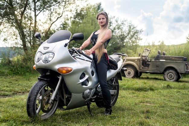 La donna attraente cammina sulla moto in estate
