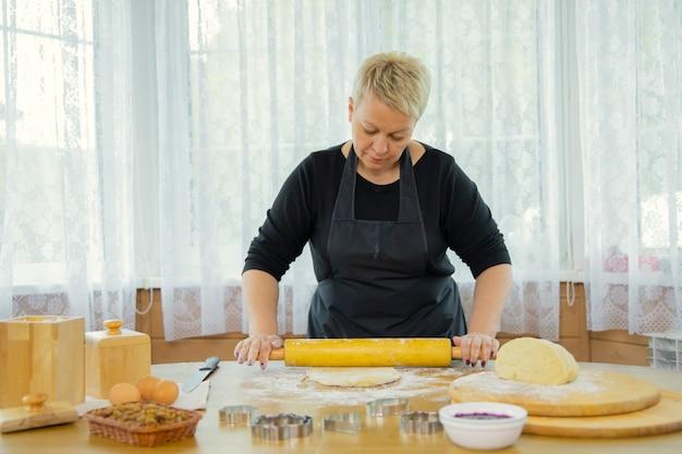 Donna attraente che porta il grembiule nero che fa i rotoli dei biscotti fatti in casa
