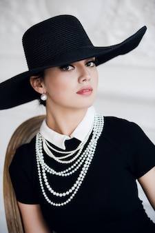 Donna attraente che indossa abito nero, cappello e perle, seduto sulla sedia