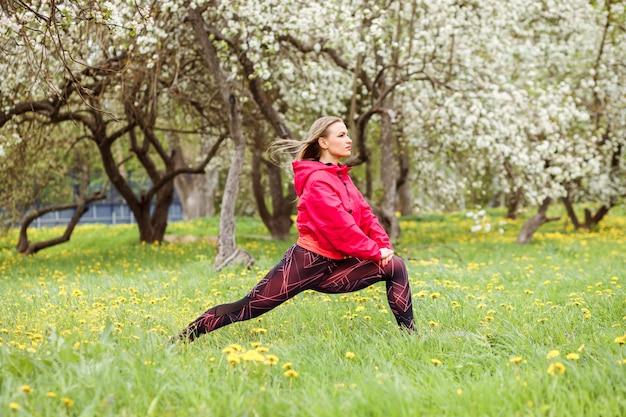 La donna attraente che indossa il bombardiere rosa sta facendo gli esercizi di forma fisica, allunganti all'aperto nel parco davanti agli alberi di fioritura