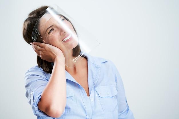 Donna attraente che indossa una maschera protettiva isolata su sfondo bianco