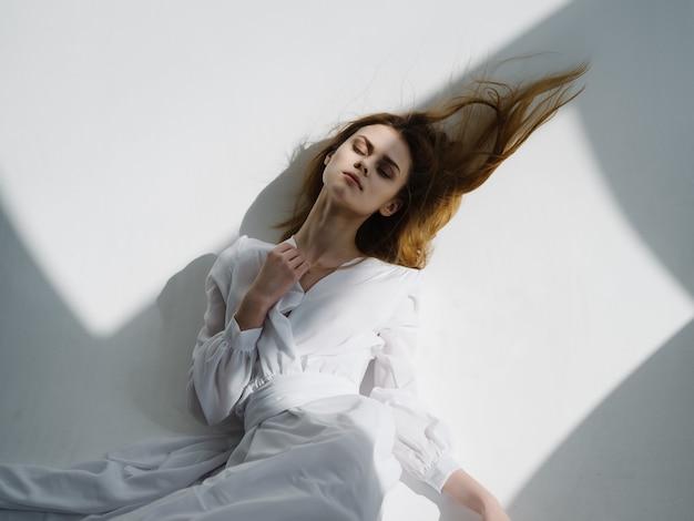 Attraente donna in abito bianco in posa isolato sfondo glamour