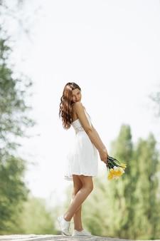 Donna attraente in vestito bianco con un mazzo di fiori primaverili in piedi contro il bokeh della natura