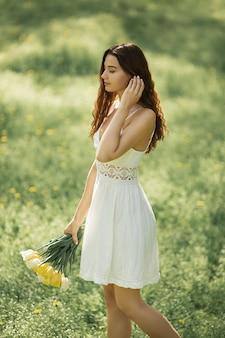 Donna attraente in vestito bianco con un mazzo di fiori primaverili che cammina contro il bokeh della natura