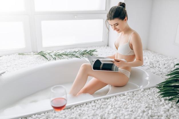 Donna attraente in biancheria intima bianca leggendo la rivista e rilassarsi nella vasca da bagno, bicchiere di vino rosso in piedi sul bordo. interno del bagno di lusso, arredamento in pietra