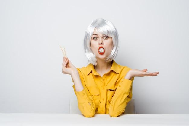 Donna attraente in parrucca bianca bacchette sushi rotoli ristorante
