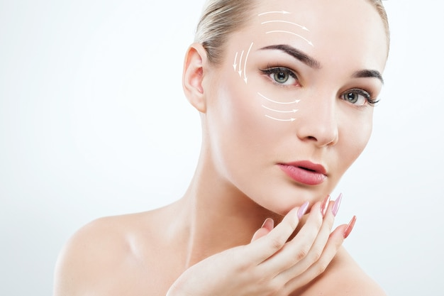 Donna attraente con grandi occhi verdi, sopracciglia scure, capelli castani e spalle nude che tengono le mani con manicure rosa Foto Premium