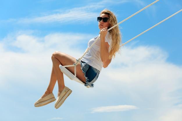 La donna attraente con capelli ricci biondi si è vestita in vestiti di estate che oscillano sulla spiaggia con fondo di cielo blu. concetto di relax e divertimento.