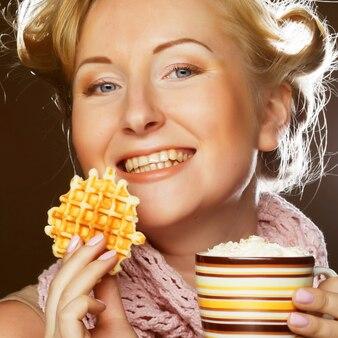 Donna attraente con caffè e biscotti Foto Premium