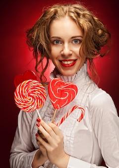 Donna attraente con caramello cuore su sfondo rosso