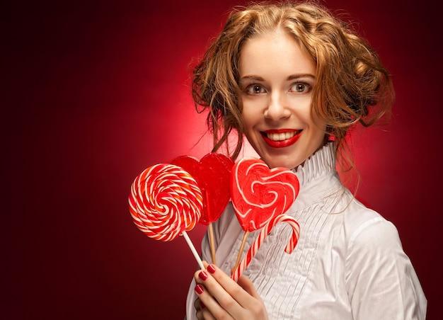 Donna attraente con caramello cuore sopra la parete rossa
