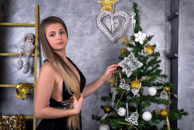 Donna attraente con capelli lunghi che posano vicino all'albero di natale