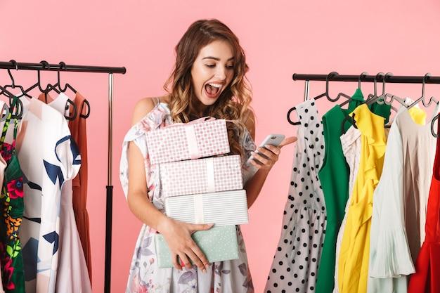 Donna attraente con acquisto in piedi nel negozio vicino a stendibiancheria e utilizzando il telefono cellulare isolato in rosa