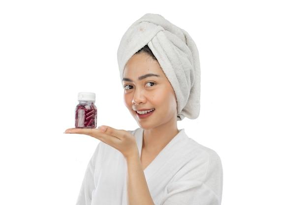 Donna attraente con asciugamano con gesto della mano che presenta una bottiglia di vitamine