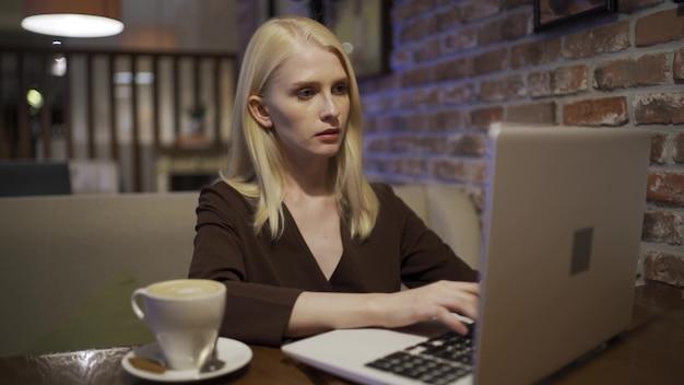 Una donna attraente lavora al computer portatile e beve un delizioso latte in un accogliente bar. lavoro a distanza, lavoro da qualsiasi parte del mondo. libertà dagli orari. primo piano, 4k uhd.
