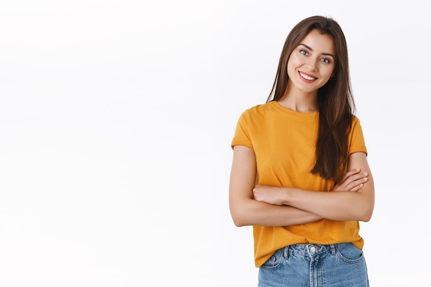 Donna attraente in maglietta gialla incrocia le mani sul petto con espressione sicura di sé e compiaciuta, inclina la testa e sorride soddisfatta, guarda un buon risultato, esulta ed esprime emozioni positive