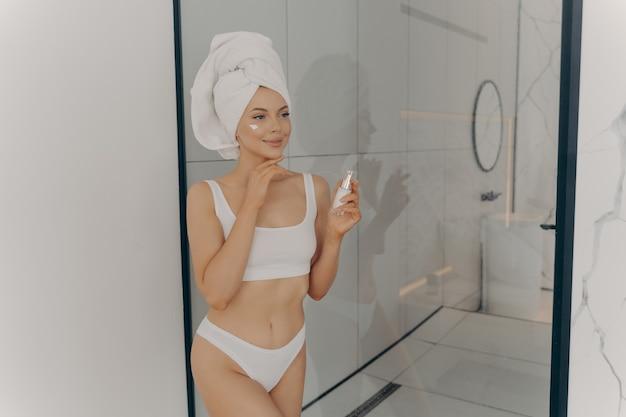 Attraente giovane donna adulta che applica la crema per il viso, bella signora sana con la testa avvolta in un asciugamano che mette crema da giorno idratante lifting nutriente sulla pelle morbida e pulita nel bagno di casa