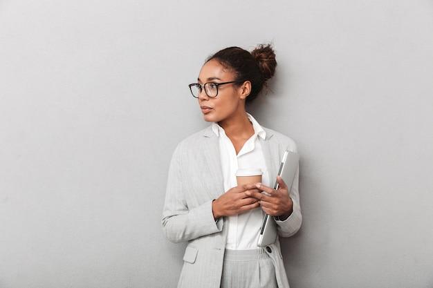 Attraente giovane donna d'affari africano in piedi isolato, tenendo tablet, bere caffè da asporto