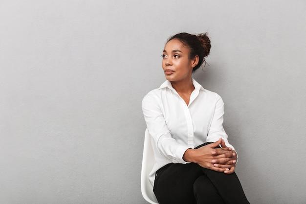 Attraente giovane africano donna d'affari che indossa la camicia seduta su una sedia isolata, guardando lontano