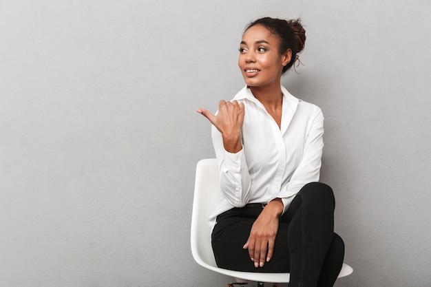 Attraente giovane africano donna d'affari che indossa la camicia seduta su una sedia isolata, indicando lontano