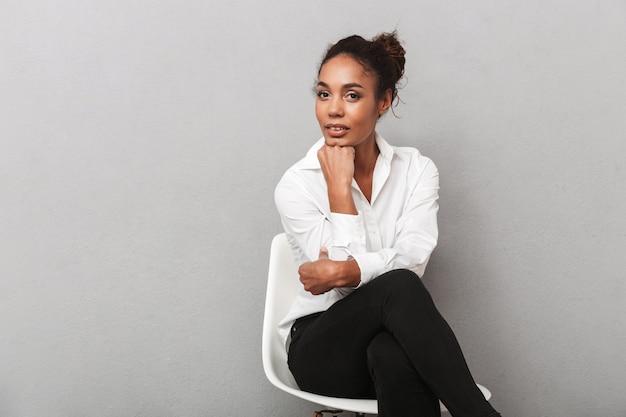 Attraente giovane africano donna d'affari che indossa la camicia seduta su una sedia isolata