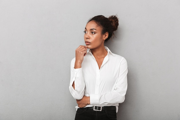 Attraente giovane africano donna d'affari che indossa la camicia in piedi isolato, guardando lontano