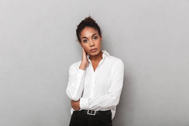 Attraente giovane africano donna d'affari che indossa la camicia in piedi isolato, alla ricerca