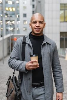 Attraente giovane africano che indossa un cappotto autunnale mentre sta in piedi per la strada della città, bevendo una tazza di caffè da asporto