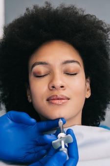 Attraente giovane donna africana sta ottenendo iniezioni facciali ringiovanenti. lei è seduta tranquillamente in clinica. l'estetista esperta riempie le rughe femminili con l'acido ialuronico.