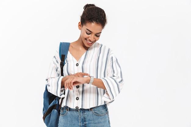 Attraente giovane donna africana che indossa abiti casual in piedi isolato su un muro bianco, portando lo zaino, controllando il tempo