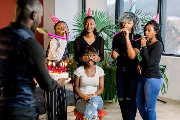 Attraente giovane donna africana con i capelli scuri, seduta sulla sedia con i suoi amici intorno a lei, festeggia e spegne le candeline di compleanno. un ragazzo africano porta una torta di compleanno con candele