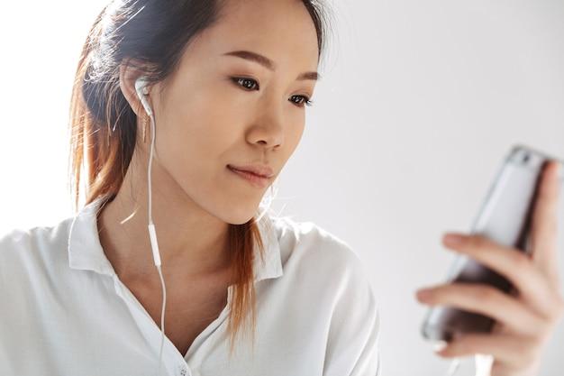 Attraente giovane imprenditrice asiatica seduta in ufficio, tenendo il telefono cellulare, con indosso gli auricolari