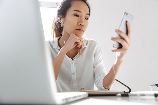Attraente giovane imprenditrice asiatica seduto in ufficio con il computer portatile tenendo il telefono cellulare, indossando gli auricolari