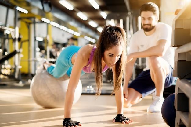 Attraente giovane ragazza atletica facendo push up con palla fitness nella moderna palestra accanto al bel personal trainer soddisfatto.