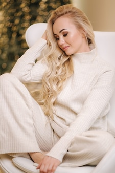 Attraente giovane donna capelli biondi in abito bianco lavorato a maglia seduto sulla sedia bianca davanti al natale
